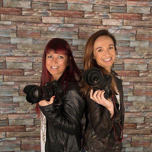 due ragazze in posa con due macchine fotografiche professionali