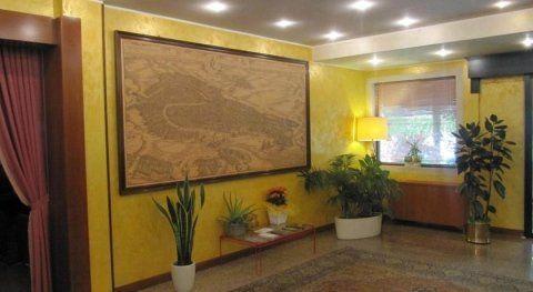 angolo di una stanza con quadro appeso alle pareti e piante