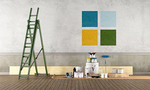 Secchi di vernice con scala a pioli di fronte a parete pitturata