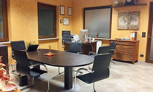 un ufficio con una grande scrivania e delle sedie nere