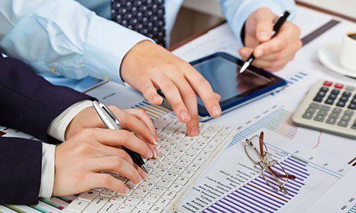 delle mani che usano dei tablet e una tastiera del computer