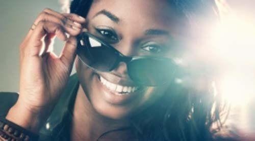 una donna sorridente mentre indossa occhiali da sole