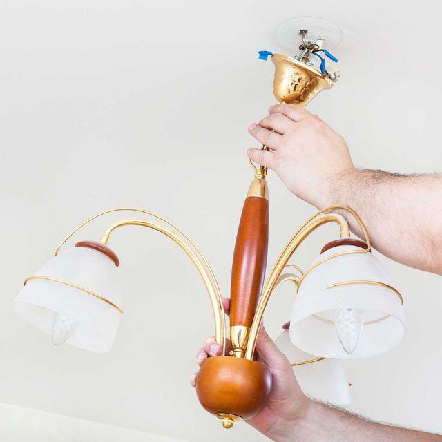 Elettricista rimuove il lampadario decorativo a soffitto per la riparazione in camera