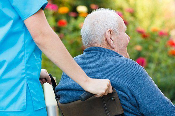 una donna che spinge la sedia a rotelle di un signore anziano