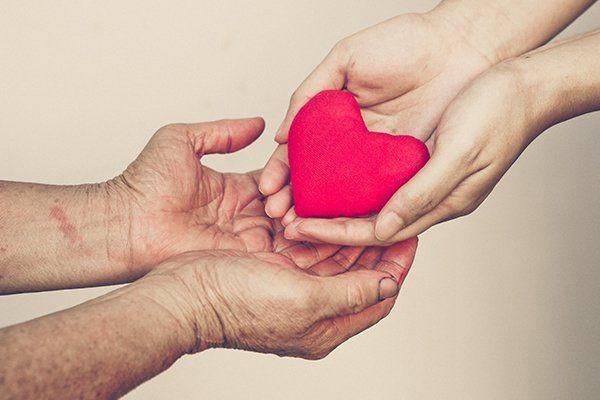 delle mani che consegnano un cuore rosso di pezza a altre due mani