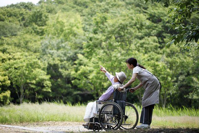 un'infermiera spinge la sedia a rotelle di un anziano