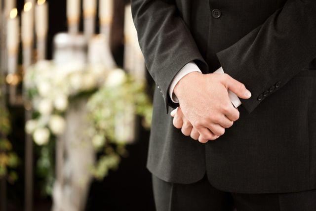 uomo vestito in nero con mani giunte, in sfondo addobbi floreali e candele