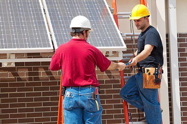 Operai stanno montando collettori solari sul tetto