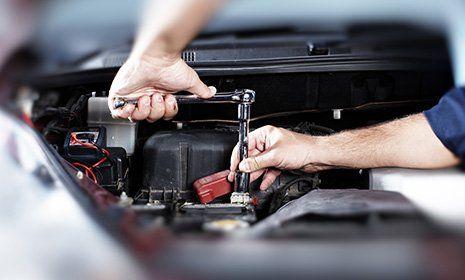 un meccanico sta riparando una vettura con il cofano aperto-OFFICINA GIACOMINI SNC -CALCERANICA AL LAGO