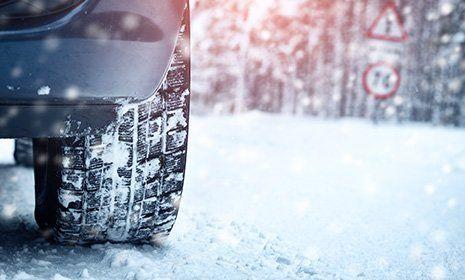 una macchina su una strada innevata con visuale focalizzzata sul pneumatico posteriore destro-OFFICINA GIACOMINI SNC -CALCERANICA AL LAGO