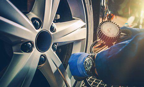 vista di una ruota e di un manometro che misura la pressione del pneumatico-OFFICINA GIACOMINI SNC -CALCERANICA AL LAGO