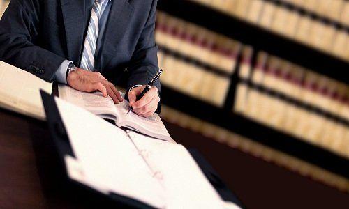 Uomo seduto a una scrivania mentre scrive, con alle spalle una libreria