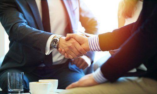 Stretta di mano tra due uomini davanti a due tazze di caffè