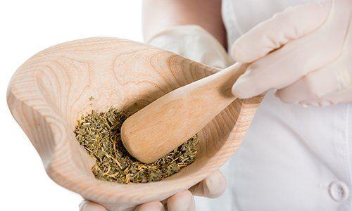 una mano con una ciotola di legno con delle erbe