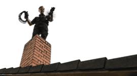 un uomo con degli attrezzi in piedi sul tetto vicino a un camino