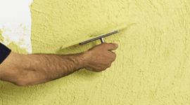 una mano che spatola un muro con della vernice gialla