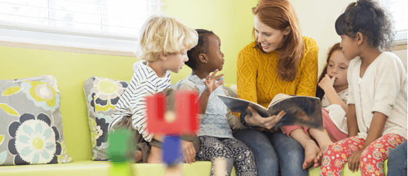 A member of the nursery staff reading to a group of children.