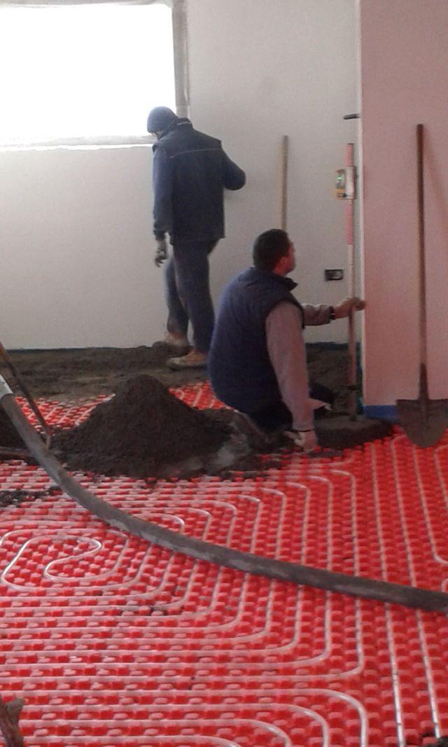 operai installano un riscaldamento a pavimento