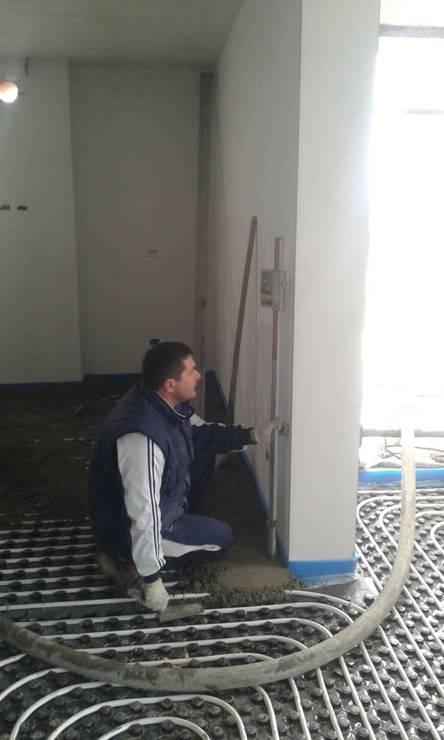 operaio installa un riscaldamento a pavimento