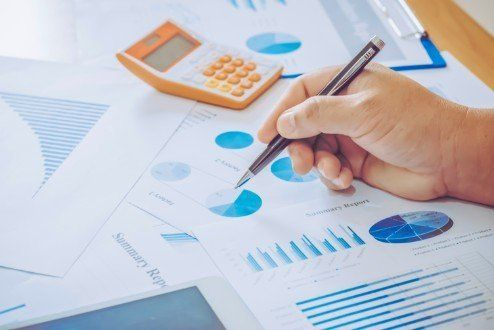 mano che tiene una penna, calcolatrice e fogli con grafici di statisitica