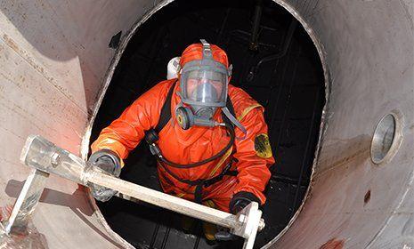 Un operaio in tuta protettiva entra in una cisterna
