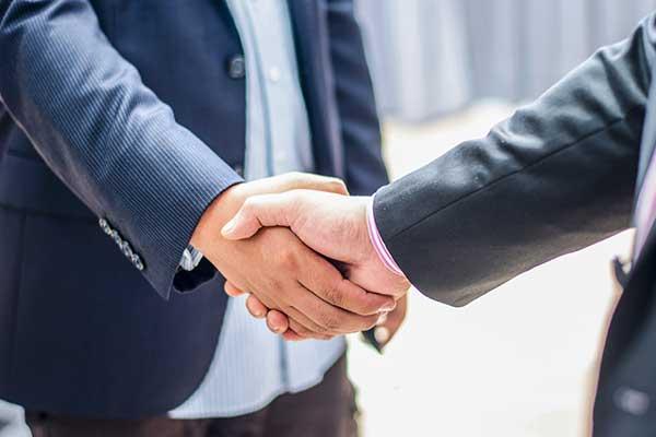vista di una stretta i mano tra due uomini in giacca e cravatta