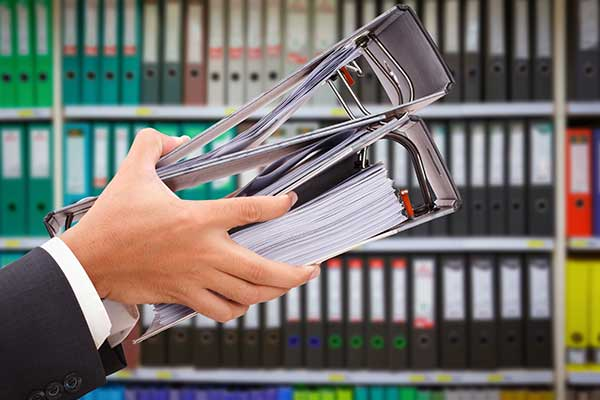 due mani con un mano due raccoglitori e dietro una libreria con tanti raccoglitori colorati infilati
