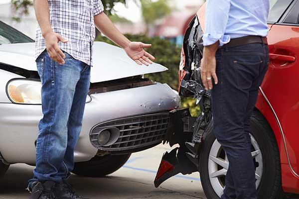 due persone discutono accanto ai loro veicoli incidentati dopo un tamponamento