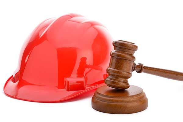 un elmetto da lavoro rosso e un martello di legno usato per le sentenze in tribunale