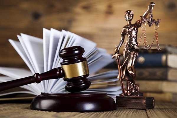 particolare del martello del giudice con statua dellla giustizia di fianco e libro aperto sullo sfondo