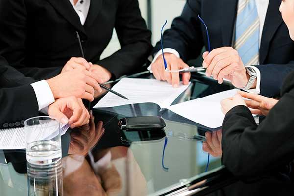 quattro uomini indicano un documento su un tavolo di vetro