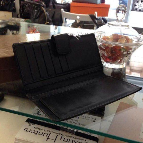 portafoglio nero aperto su una scrivania in vetro