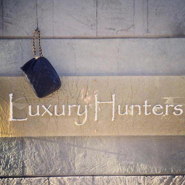 portamonete in pelle e insegna Luxury Hunters