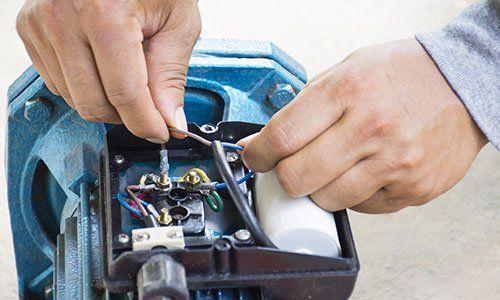 due mani stanno riparando la parte elettrica di un motore