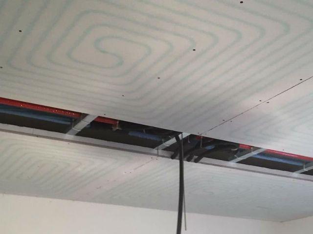 delle tubature visibili da un soffitto con dei pannelli non ancora finito