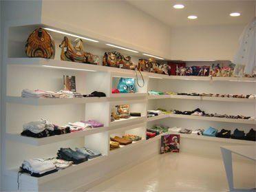 dei vestiti piegati su delle mensole a muro