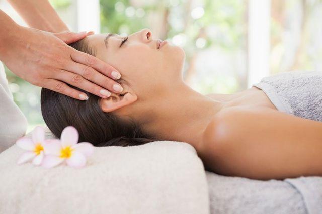 una donna sdraiata e dietro una massaggiatrice che le massaggia le tempie