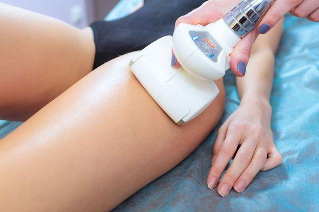 vista di una coscia di una donna e un dispositivo di epilazione elettronico
