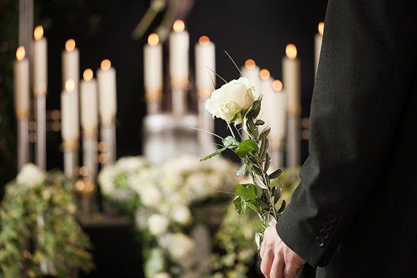 Il fondo candele accese e in primo piano una mano a sostenere una rosa bianca