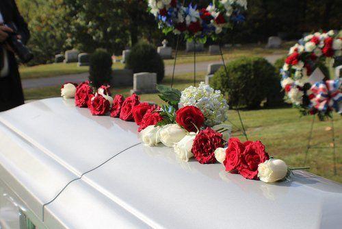 addobbi floreali su una bara bianca in un cimitero