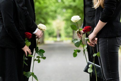 persone in piedi al funerale con i fiori