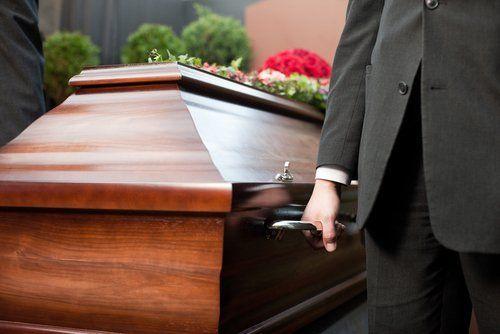persona che tiene una bara funebre in legno
