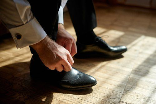 Uomo che allaccia delle scarpe in pelle nera eleganti