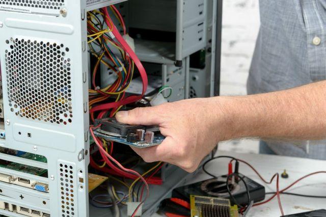 Una mano cche inserisce una scheda elettronica all'interno del case di un pc fisso