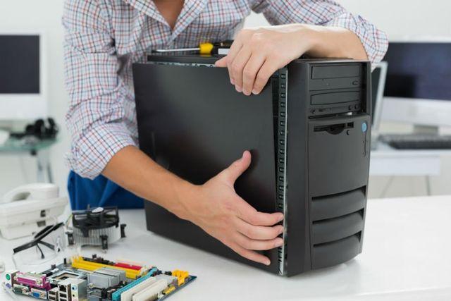 Un tecnico mentre chiude il case di un computer fisso dopo aver rimosso una scheda madre
