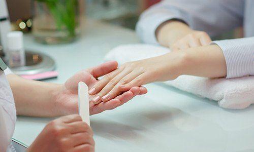 Una estetista mentre lima le unghie di una donna con una lima di cartone