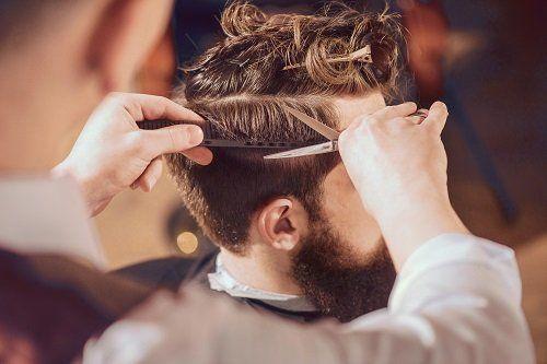 una mano con un pettine e l'altra con una forbice durante un taglio di capelli a un uomo