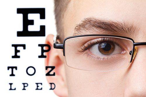 ragazzo con occhiali e immagine della tabella per misurazione vista