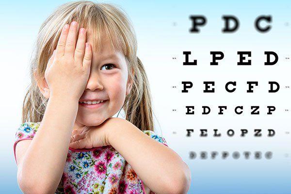 una bambina che si copre un occhio e delle lettere