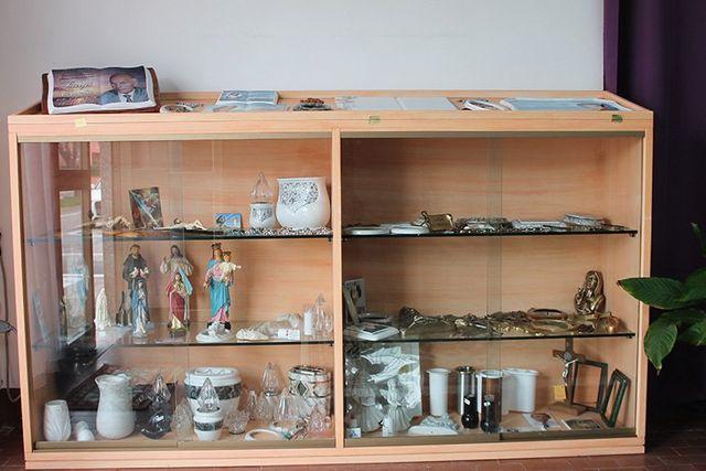 un mobile vetrina con dentro degli oggetti e delle statuette di figure religiose